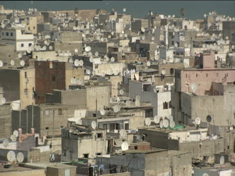 Pan left across flat roofs of densely built houses covered with satellite dishes and washing lines Casablanca