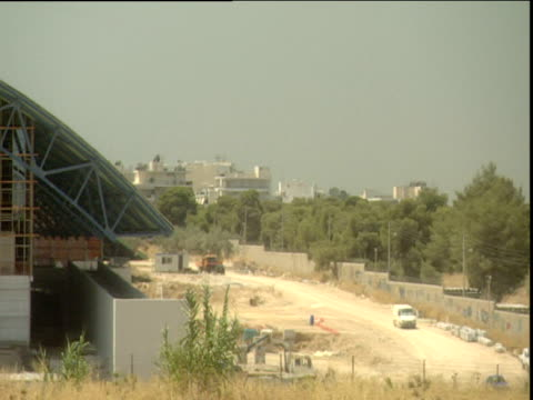 pan left across galatsi stadium in construction which is the venue for rhythmic gymnastics and table tennis events in the 2004 olympics athens - erezione video stock e b–roll