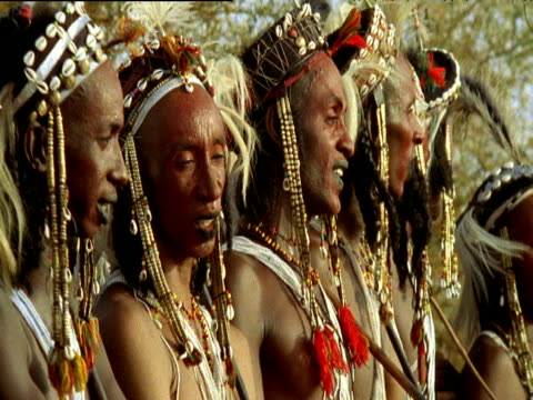 pan left across male wodaabe tribesmen as they chant in line during cultural ritual ingal niger - ニジェール点の映像素材/bロール