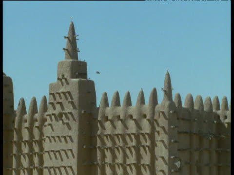 Pan left across minarets and pinnacles of mud-brick Great Mosque of Djenne, Mali