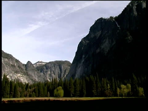 pan left across mountains cliff faces and trees - felswand stock-videos und b-roll-filmmaterial