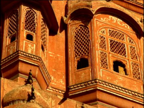 vídeos de stock, filmes e b-roll de pan left across ornate bay windows on exterior of hawa mahal - 'palace of the winds' jaipur - janela saliente