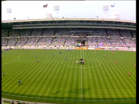 pan left across packed stands of wembley as players warm up on pitch liverpool vs wimbledon 1988 fa cup final wembley london - competizione video stock e b–roll