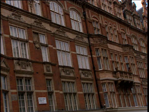 Pan left across red brick building with numerous windows to corner London
