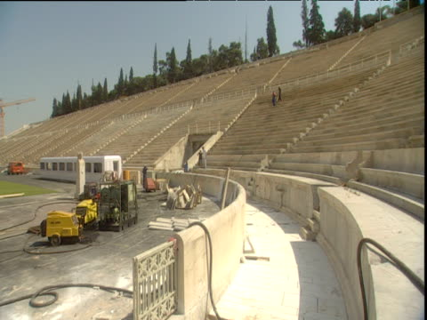 pan left across renovation workers restoring the panathinaikon stadium for the 2004 olympic games athens - panathinaiko stadium stock videos & royalty-free footage