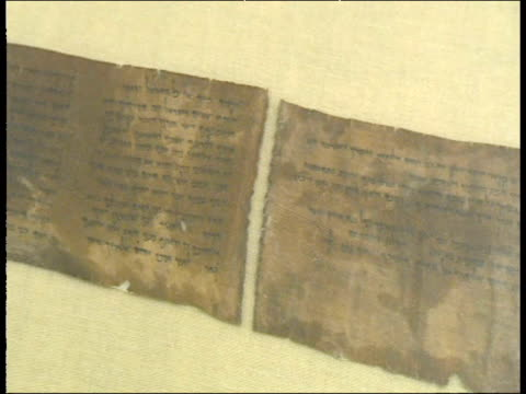 pan left across scroll from book of deuteronomy in museum containing ten commandments found in caves of qumran west bank - arte dell'antichità video stock e b–roll