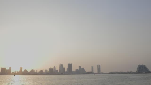 pan left across the manama skyline at sunset. - ペルシャ湾点の映像素材/bロール