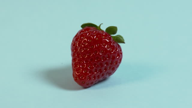 pan left across, then pan right across, a single strawberry on a plain pale blue background. - single object stock videos & royalty-free footage