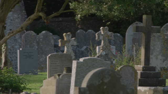 pan left across tombstones in a graveyard - cemetery stock videos & royalty-free footage