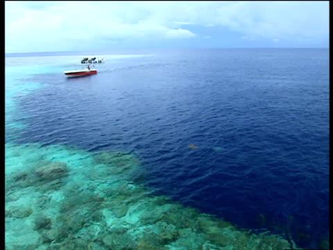 pan left across turquoise blue sea to sandy shore and boats sipadan - ボルネオ島点の映像素材/bロール