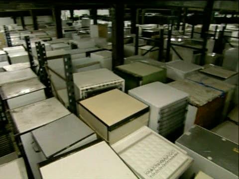 Pan left across warehouse full of discarded fridges UK 25 May 04