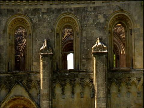 pan left across window frames of glastonbury abbey ruins somerset - glastonbury abbey stock videos & royalty-free footage
