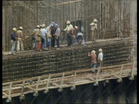 pan left across workers at construction site of itaipu dam brazil - erezione video stock e b–roll
