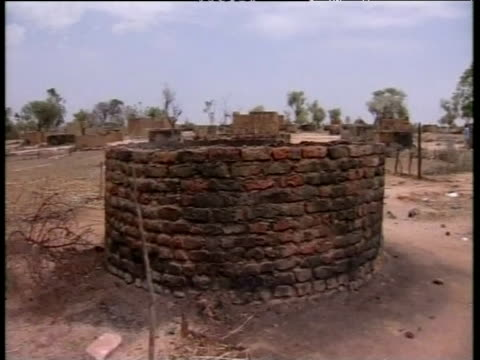 Pan left across wreckage of abandoned village Darfur Jun 04