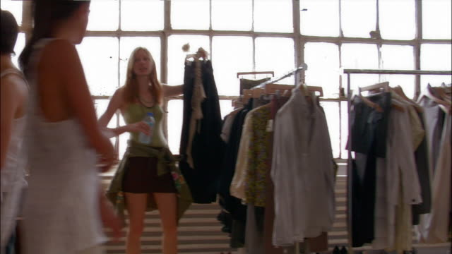 pan left across young design team selecting clothes off rack in loft atelier / pan right - atelier fashion stock videos & royalty-free footage