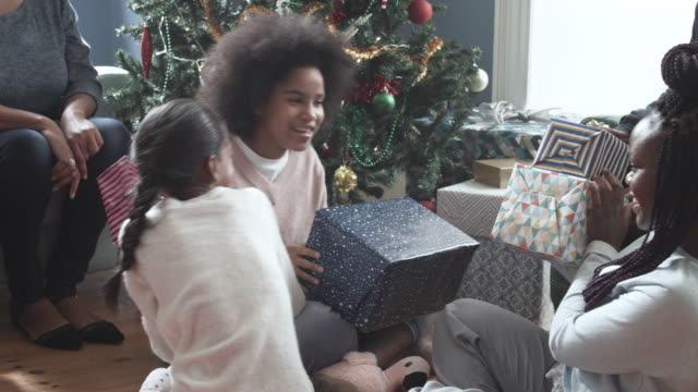 Pan left, African American grandparents record children opening gifts on Christmas