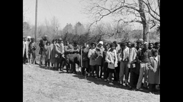 vídeos de stock, filmes e b-roll de pan left along a queue of marchers outside a hotel on the route from selma to montgomery; 22nd march 1965. - 1965