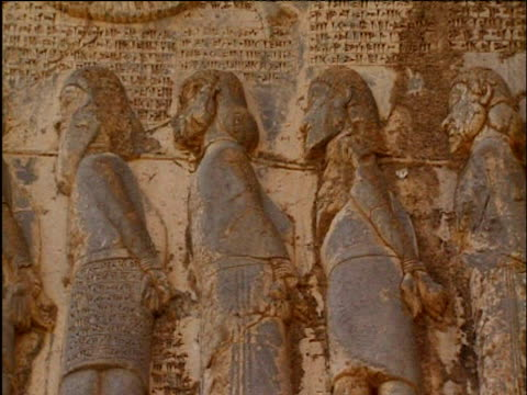 pan left along ancient sculptures on walls of monument of darius bisitun - iran stock videos and b-roll footage