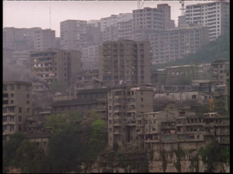 Pan left along tatty high rise apartment buildings piled up on bank of Yangtze River Chongqing China