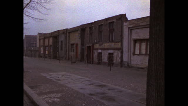 pan left along the berlin wall and closed shop fronts along an urban road in berlin; 1969. - national landmark stock videos & royalty-free footage