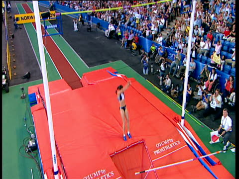 Pan left and crane up as Yelena Isinbayeva clears bar at 490m to set new World Record Isinbayeva celebrates with a somersault and punches the air...