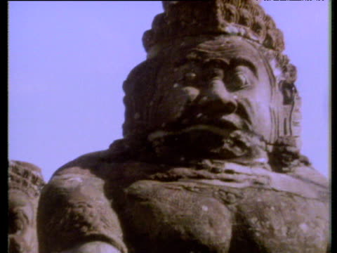 pan left and down from face of stone statue along row of statues angkor wat - cambodia stock videos and b-roll footage