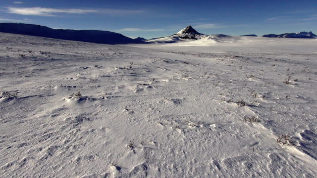 WS pan left and right of snowdrift covered prairie landscape with mountains in background.