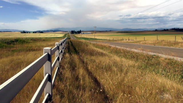 Pan left and right of white rail style country fence on gravel road in country.