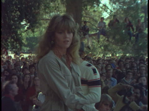 pan left and zoom in to jane fonda on stage as she is cheered and booed by rally attendees - ジェーン・フォンダ点の映像素材/bロール