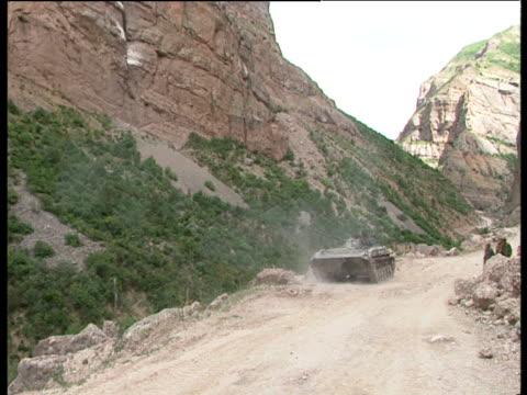 pan left and zoom to point of impact as tank fires into steep mountainside tajikistan civil war tajikistan 1992 - ムラがある点の映像素材/bロール