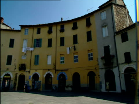 stockvideo's en b-roll-footage met pan left around piazza anfiteatro lucca including colourful cream and yellow houses as man rides through square past small cafes on bike - toscane