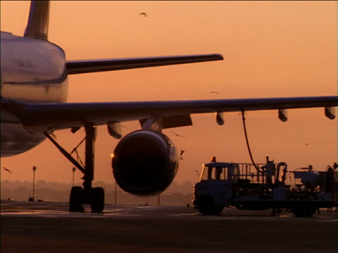 pan left as aircraft is refuelled on runway at sunset - tanken stock-videos und b-roll-filmmaterial