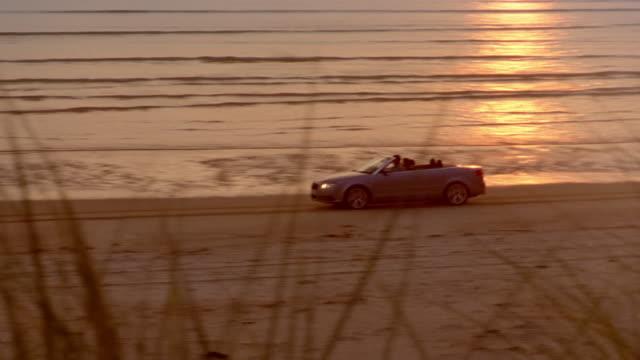 pan left as convertible car drives along beach at sunset / scotland - prestige car stock videos & royalty-free footage