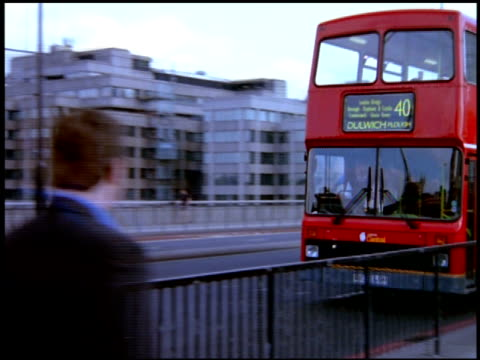Pan left as double decker bus and pedestrians pass over London Bridge, London