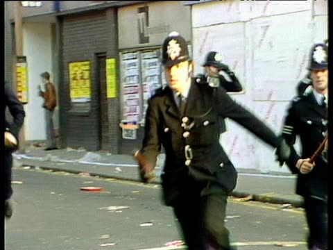 vídeos de stock e filmes b-roll de pan left as four police officers with truncheons avoid objects being thrown and chase young man through crowded street during riots brixton; apr 81 - 1981