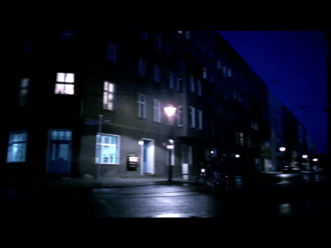 pan left as man cycles around corner on empty residential street berlin - straßenlaterne stock-videos und b-roll-filmmaterial