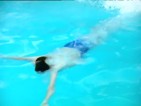 pan left as man swims underwater in swimming pool - human limb stock videos & royalty-free footage
