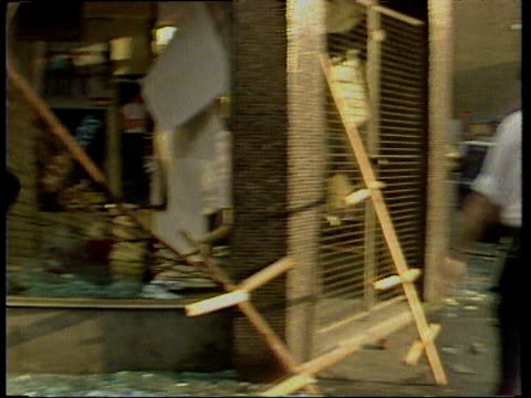 pan left as policeman throws bust then legs of mannequin into broken shop window front during clean-up operation after rioting in brixton london; apr... - 1981 stock videos & royalty-free footage