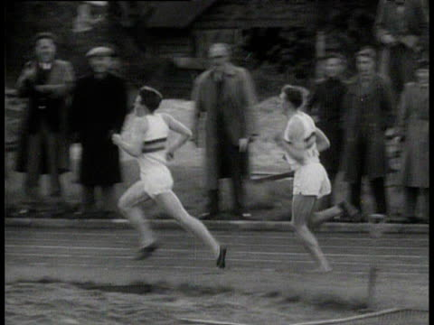 pan left as roger bannister overtakes pace setter chris chataway to become the first man to run a mile in under four minutes crowd cheer bannister on... - マイル点の映像素材/bロール