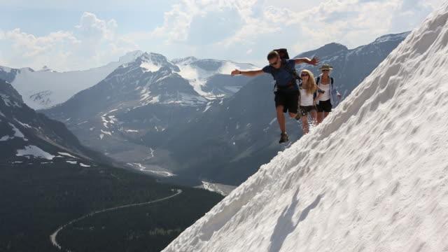 vídeos de stock e filmes b-roll de pan left as young hiker jumps off a snow cornus and slides to the bottom laughing - cornus