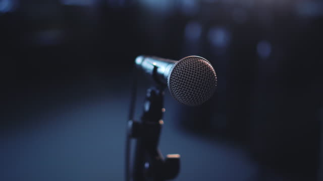 pan left close up microphone in room with spotlight - music stock videos & royalty-free footage