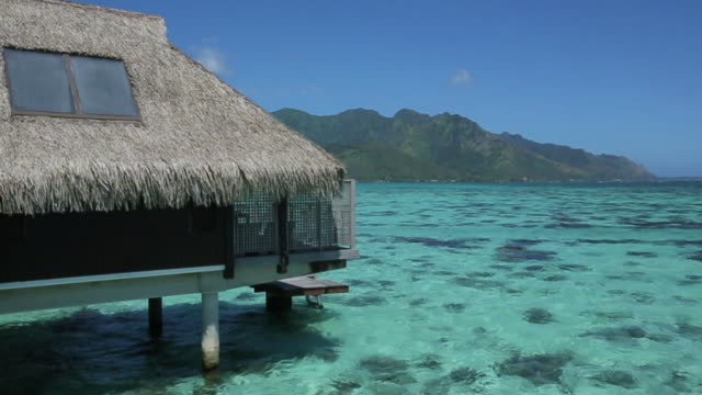 vídeos de stock e filmes b-roll de pan left, coastal huts in tahiti - polinésia francesa