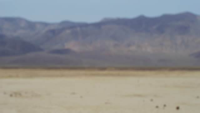 Pan left, desert mountains in distance