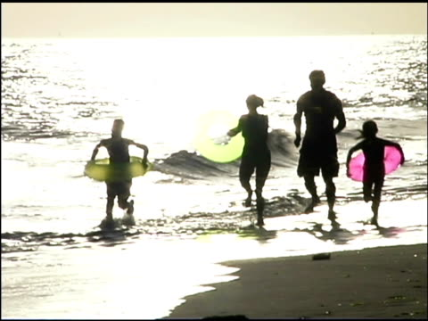 pan left follow of a family running in the ocean surf at sunset. they are wearing bathing suits and the mother, son, and daughter are carrying innertubes. - see other clips from this shoot 1135 stock videos & royalty-free footage