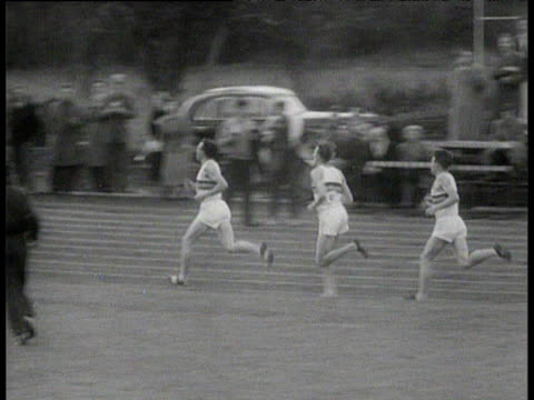 pan left following chris brasher dropping back as chris chataway moves into pace setting position roger bannister remains second crowd cheer runners... - world record stock videos & royalty-free footage