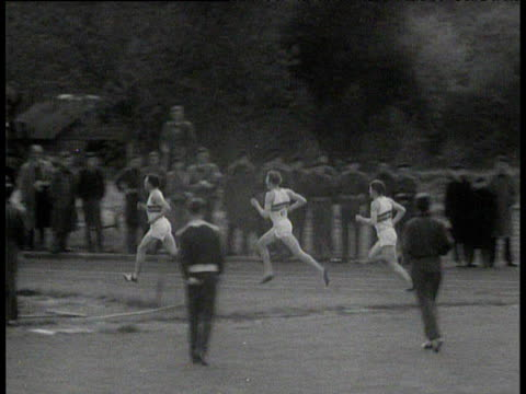 pan left following chris brasher leading roger bannister and chris chataway during bannister's sub 4 minute mile crowd look on from side of track... - マイル点の映像素材/bロール