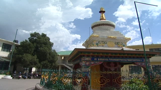 pan left from a stupa surrounded by a fence decorated with yin yang symbols to the exterior of the central tibetan administration. - traditionally tibetan stock videos & royalty-free footage
