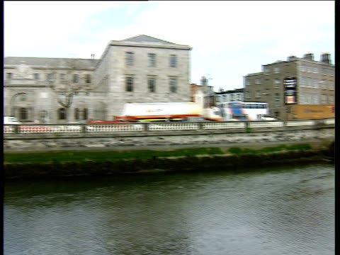 vidéos et rushes de pan left from bridge over river liffey to four courts building with traffic outside - fronton