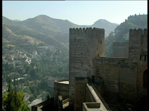 vídeos de stock, filmes e b-roll de pan left from castle towers to town in valley below granada - castelo