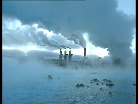Pan left from chimneys with steam billowing out to blue water with more steam Blue Lagoon Iceland
